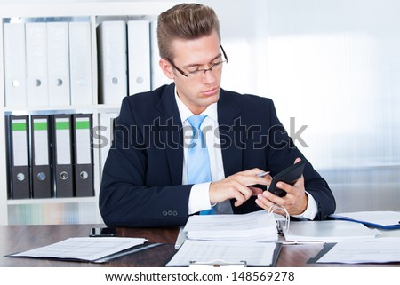 Portrait Of Young Businessman Using Calculator In Office - stock photo