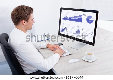 Portrait Of Young Businessman Using Computer At Desk - stock photo