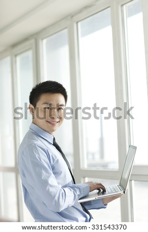 Portrait of young businessman using laptop in corridor