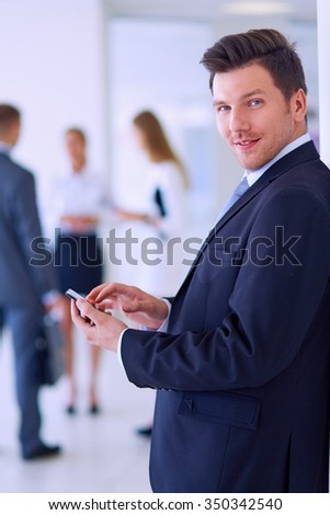 Portrait of young businessman using mobile in office with colleagues in the background - stock photo