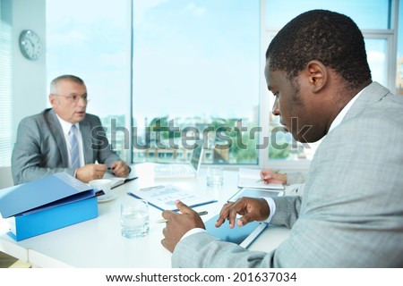 Portrait of young businessman using touchpad at meeting - stock photo