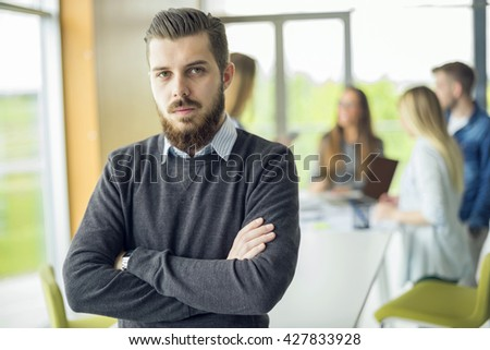 Portrait of young businessman with arms crossed  - stock photo