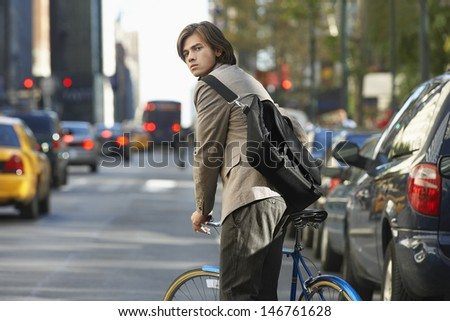 Portrait of young businessman with bicycle on busy street - stock photo