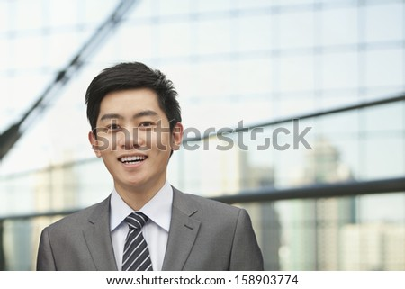 Portrait of young businessman with cityscape in background - stock photo