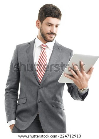 Portrait of young businessman with digital tablet standing against white background.