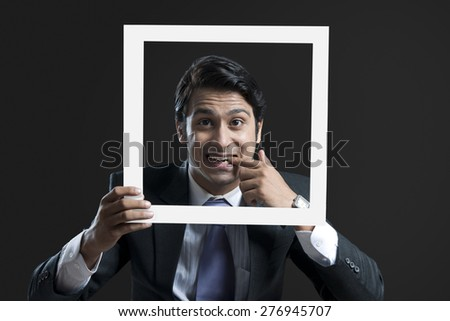 Portrait of young businessman with finger in mouth holding frame against black background