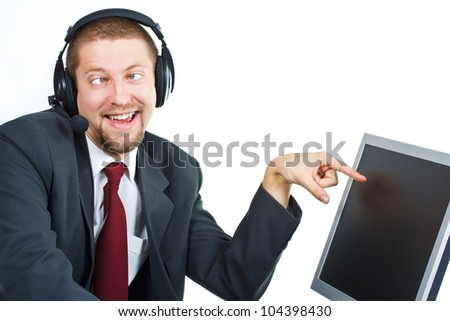 Portrait of young businessman with funny grimace with headset showing and smiling at a monitor - isolated on white