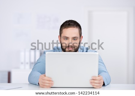 Portrait of young businessman with laptop at desk - stock photo
