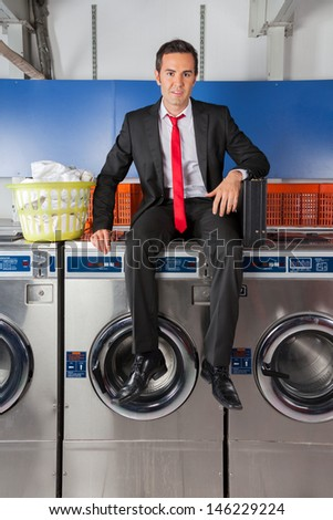 Portrait of young businessman with suitcase and clothes basket sitting on washing machine in laundry