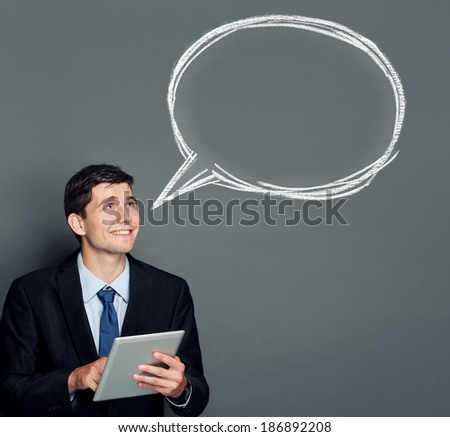 portrait of young businessman with tablet pc looking up to copy space