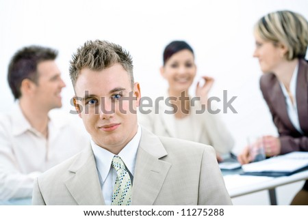 Portrait of young businessman with three colleagues sitting in background. - stock photo