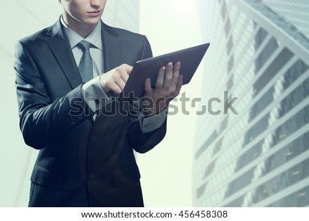 Portrait of young businessman with touch screen computer, in an urban setting - stock photo