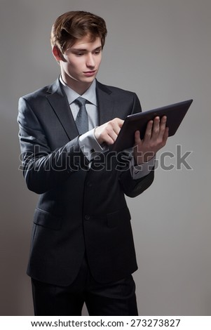 Portrait of young businessman with touch screen computer, on gray background