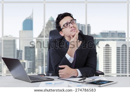 Portrait of young businessman working in the office while thinking a plan