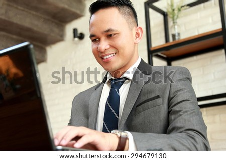 portrait of young businessman working on his laptop - stock photo
