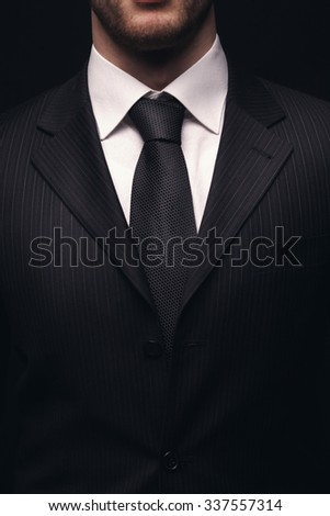 Portrait of young businessmen suit isolated on dark background - stock photo