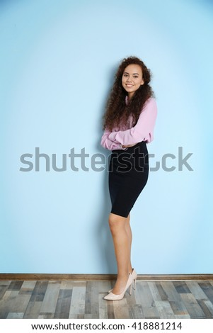Portrait of young businesswoman against blue wall background - stock photo