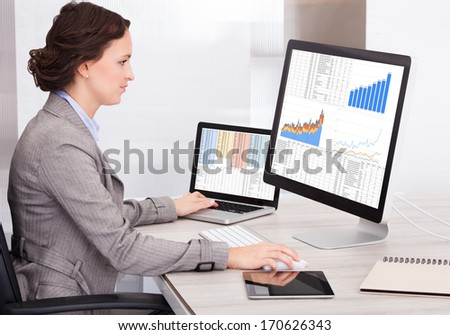 Portrait Of Young Businesswoman Analyzing Graph On Computer