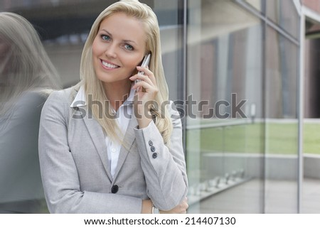 Portrait of young businesswoman communicating on cell phone while leaning on glass wall - stock photo