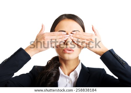 Portrait of young businesswoman covering eyes with hands. - stock photo