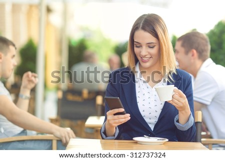 Portrait of young businesswoman drinking coffee and using mobile phone while sitting at the sidewalk cafe - stock photo