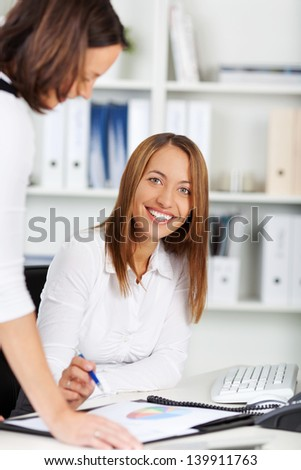 Portrait of young businesswoman explaining coworker at office desk