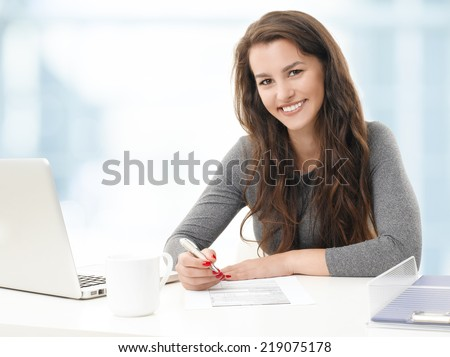 Portrait of young businesswoman fill the form while sitting at office. - stock photo