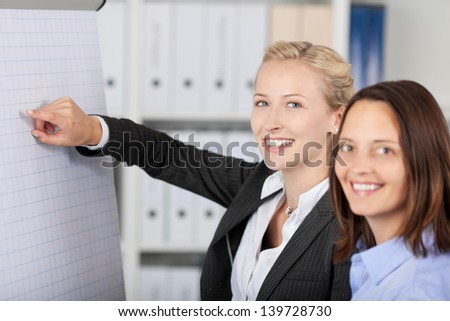 Portrait of young businesswoman giving presentation while standing with coworker in office - stock photo