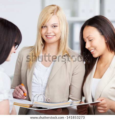 Portrait of young businesswoman holding binder with female coworkers looking at it in office