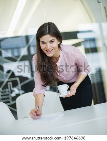 Portrait of young businesswoman holding coffee at desk in office - stock photo