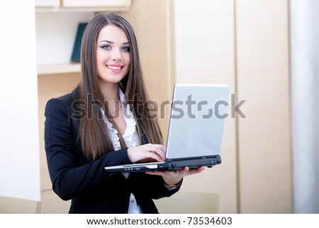 Portrait of young businesswoman holding laptop and smiling to you