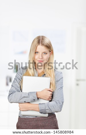 Portrait of young businesswoman holding laptop while standing in office - stock photo