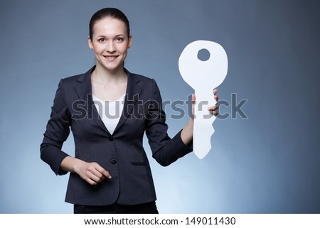 Portrait of young businesswoman holding paper key and looking at camera - stock photo