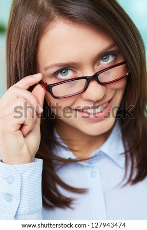 Portrait of young businesswoman in eyeglasses looking at camera and smiling - stock photo