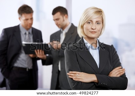 Portrait of young businesswoman in office lobby, smiling. Colleagues talking in the background. - stock photo