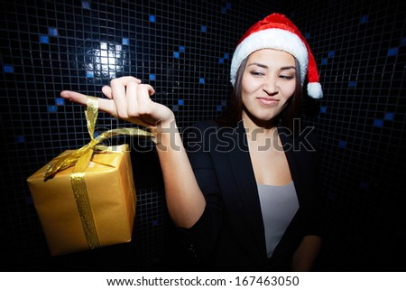 Portrait of young businesswoman in Santa cap holding Chistmas gift and looking at it with sneer - stock photo