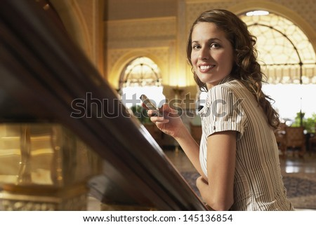 Portrait of young businesswoman leaning on railing holding mobile phone - stock photo