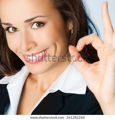 Portrait of young businesswoman showing okay gesture, against blue background - stock photo