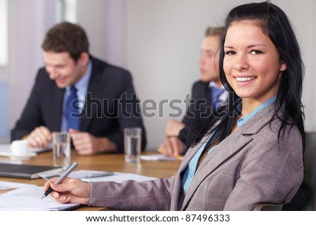 Portrait of young businesswoman sitting at conference table during business meeting