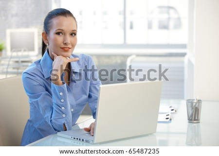 Portrait of young businesswoman sitting at office desk with laptop computer, smiling confidently at camera.? - stock photo