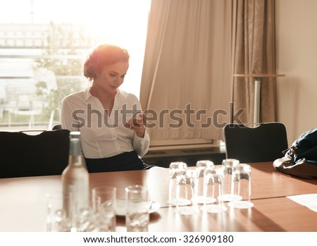 Portrait of young businesswoman sitting in business conference room using mobile phone. Female executive sitting in hotel conference room reading text message on her mobile phone. - stock photo