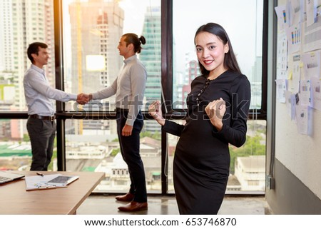 Portrait of young businesswoman smiling at camera on background of working people