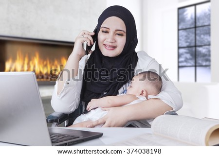 Portrait of young businesswoman talking on the phone while holding her little baby boy - stock photo
