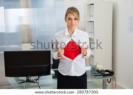 Portrait Of Young Businesswoman Tearing Her Shirt Revealing A Superhero Suit - stock photo