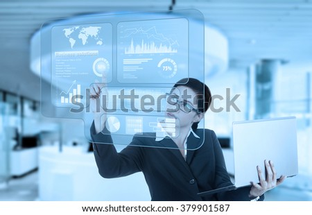 Portrait of young businesswoman using a virtual screen to make financial statistics while holding laptop in the office