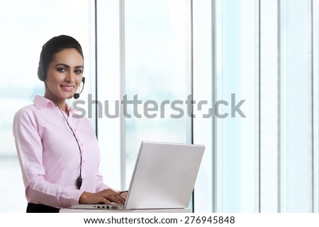 Portrait of young businesswoman using headset and laptop at office - stock photo