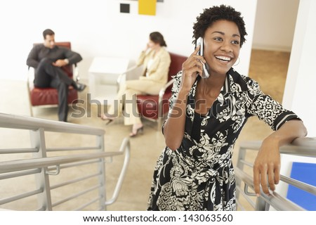 Portrait of young businesswoman using mobile phone on stairway with colleagues discussing in background