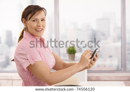 Portrait of young businesswoman using smartphone in office, looking at camera, smiling.?