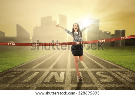 Portrait of young businesswoman winning the competition and crossing the finish line with numbers 2016