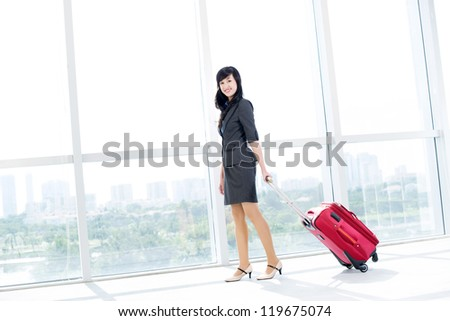 Portrait of young businesswoman with baggage looking at camera in airport - stock photo